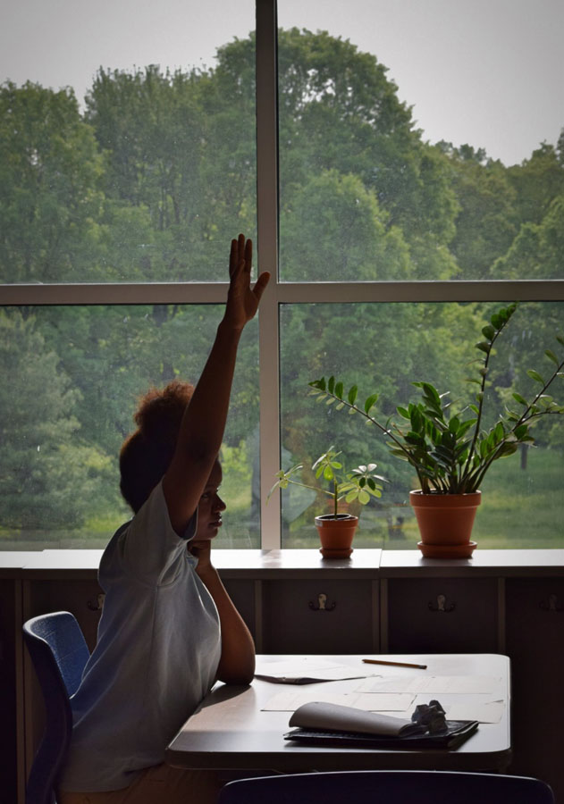 A KIPPster raising her hand in class at KCM overlooking the back of KCM.