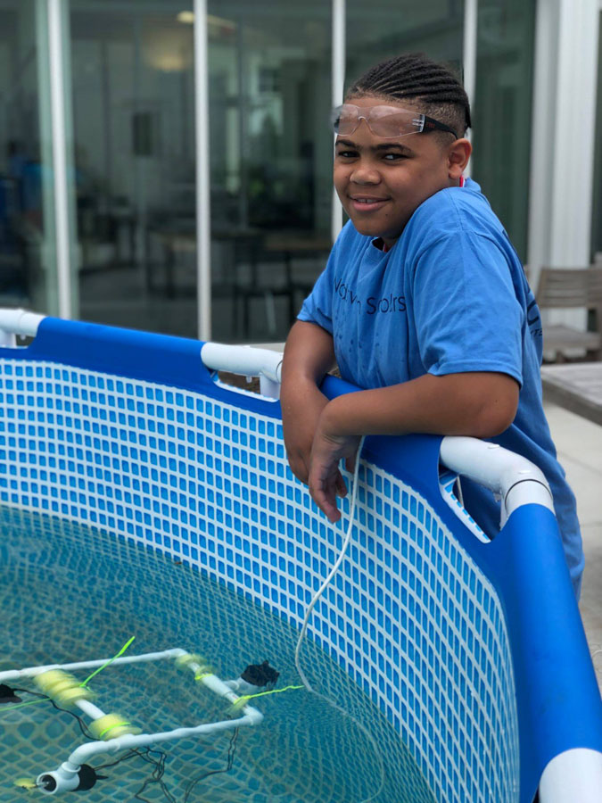 A KIPPster testing his underwater robot during a PAST Foundation STEM summer camp on the outdoor patio of the Battelle Environmental Center.