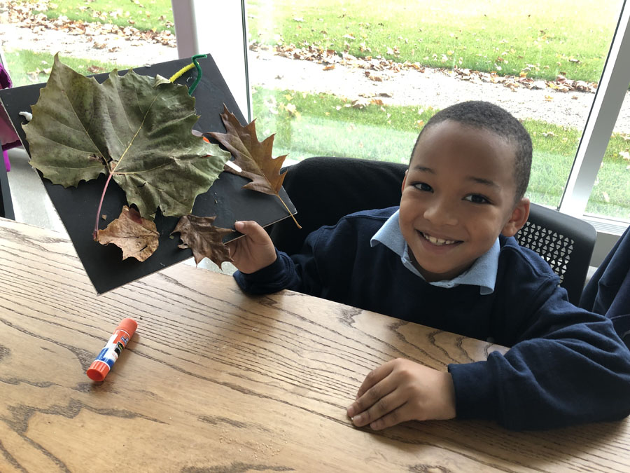 A KIPPster exploring fall leaves in the Battelle Environmental Center.